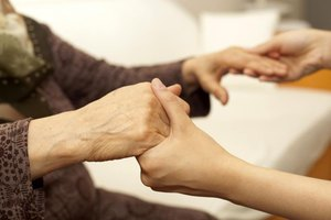 Young woman's hands holding an elder woman's hands.