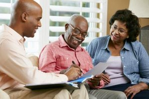 Financial advisor speaking to a mature couple at home