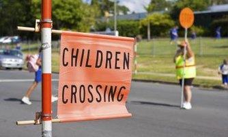 """Children Crossing"" sign with cross guard in background"