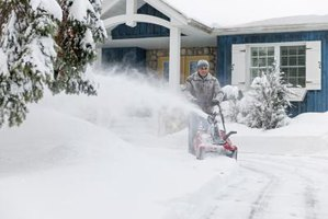 Man using snowblower to clear his driveway.