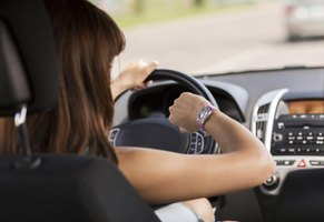 A woman is looking at her watch while driving a car.