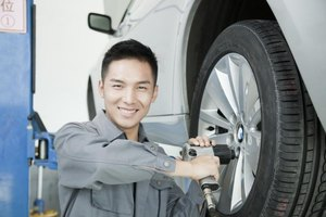 Smiling mechanic changes tires on a car.