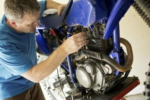 Close-up of a mechanic working on a motorcycle engine