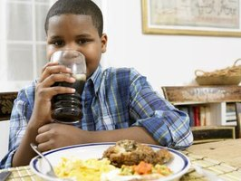 A boy is drinking a glass of soda.