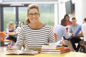 Adult in classroom with stack of books