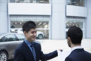 Salesman giving keys of new car to buyer