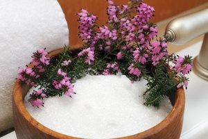 Bowl of Epsom salts and pink flowers.