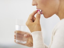 Woman taking a vitamin supplement with a glass of water.