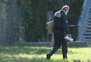 A  policeman carrying evidence collected at a crime scene.