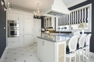 A crystal chandelier, tile flooring and painted antique chairs in an art deco style kitchen.