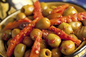 Bowl of olives with harissa sauce on them