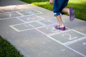 Student jumping on hopscotch drawing on sidewalk.