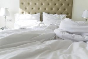A white alternative down comforter on a bed in the morning.