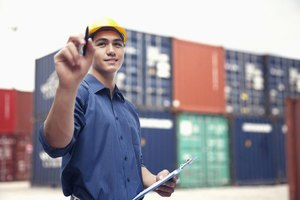 A dock worker is standing by containers.