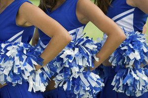 Close-up of cheerleaders holding pompoms at their sides