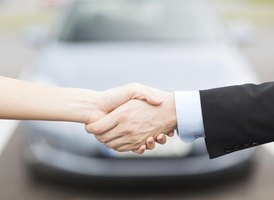 Handshake in front of a car