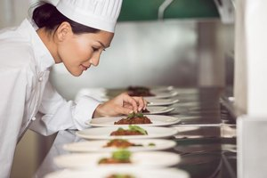 A chef prepares plates at a catered event.