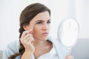 Woman plucking her eyebrows in small hand mirror.