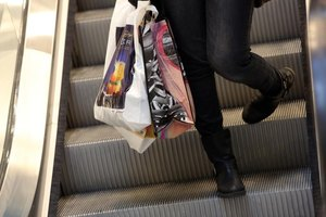 A woman carrying department store shopping bags down the escalator in a mall.