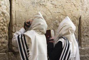 Two men wear prayer shawls as they pray towards the Western Wall in Jerusalem