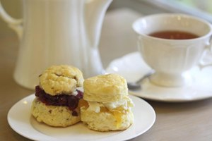 Scones served with fruit jams and hot tea.
