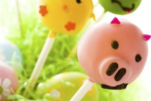 Make simple piggy cake pops with pink candy melts and brown piping.