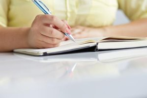 Close-up of woman writing in notebook