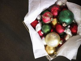 An overhead view of a basket of red, green, white and gold Christmas ornaments.