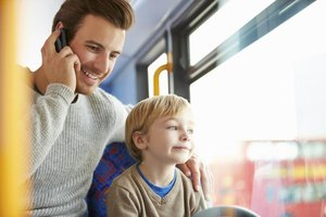 A father talking on the phone while riding a city bus with his son.