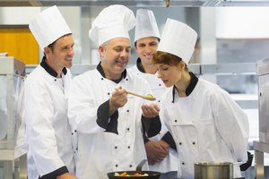 Culinary students in kitchen with teaching chef.