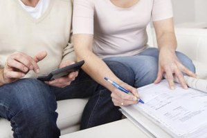 Elderly couple going through tax paperwork at home.