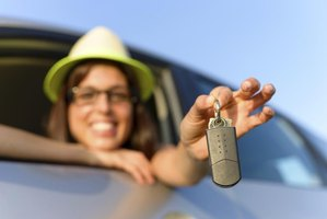 Woman driver holding the key to a new car.