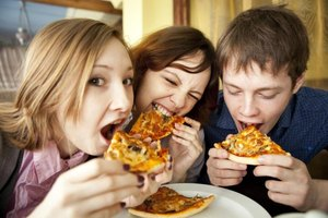 Three teenagers eating pizza together.