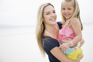 Mother holding stepdaughter on beach.