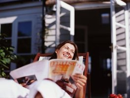A woman smiling while looking at a magazine on her patio.