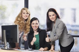 Employees giving thumbs up at desk