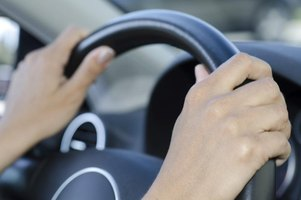 Woman's hands holding a steering wheel.