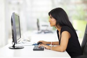 Woman typing on desktop computer