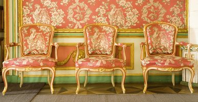 Three Victorian parlor chairs against a wall with matching wallpaper.