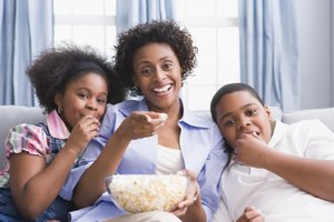 Family eating popcorn while watching tv.