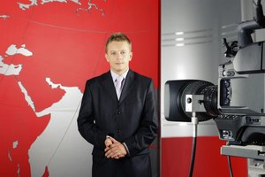 A news anchor being filmed in a studio.