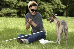 A blind woman is playing with her dog.