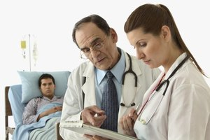 Nurse going over patient's chart with doctor.