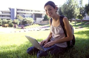 Student on grass with laptop