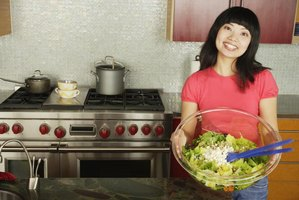 Woman holding large salad bowl in kitchen.