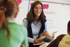 Smiling teacher holding book in classroom