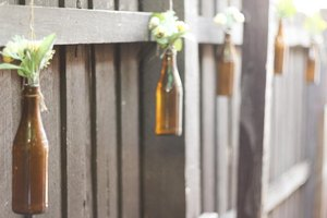 Amber bottles filled with flower clippings hanging from a backyard fence.