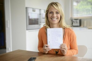 A woman smiling at the kitchen table with a to do list.