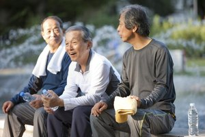 Three men socializing on an outdoor bench.