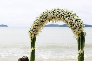 A flower arch set up for a wedding on a beach in Thailand.